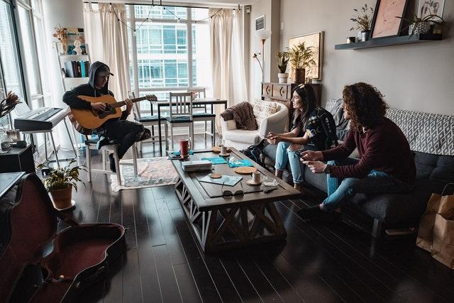 lidé v obývacím pokoji, jeden muž sedí s kytarou